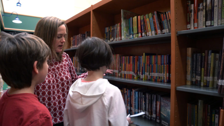 Instructor from Elmbrook School District shows students books from the school library.