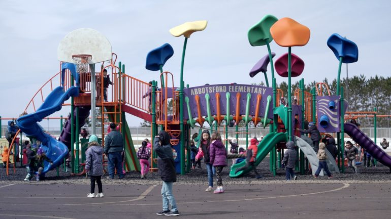 Children play on a jungle gym at Abbotsford Elementary School.