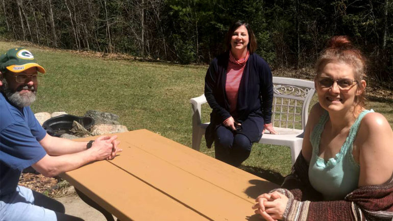 A man and two women sitting around a picnic table