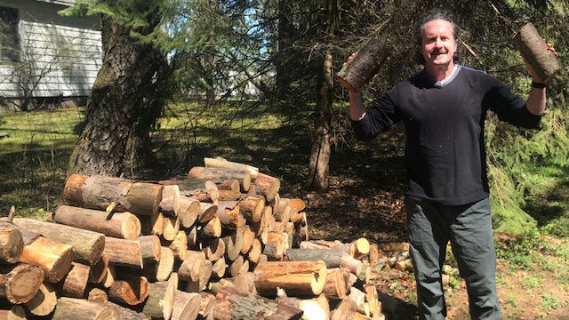 Man standing next to pile of split wood