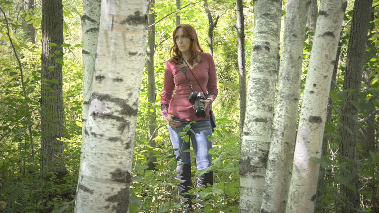 Woman with camera standing in the woods
